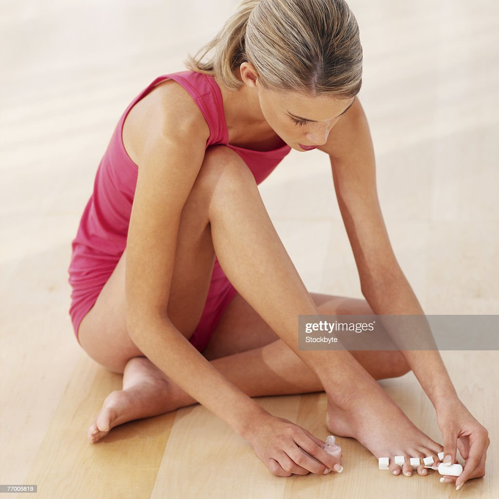 Young woman painting toenails, high angle view : Stock Photo
