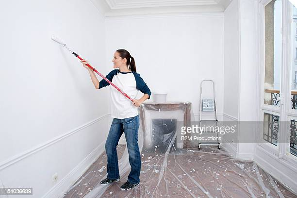Young Woman Painting Wall With Paint Brush