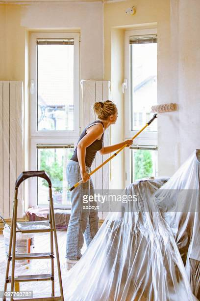 Young woman painting wall with telescopic roller