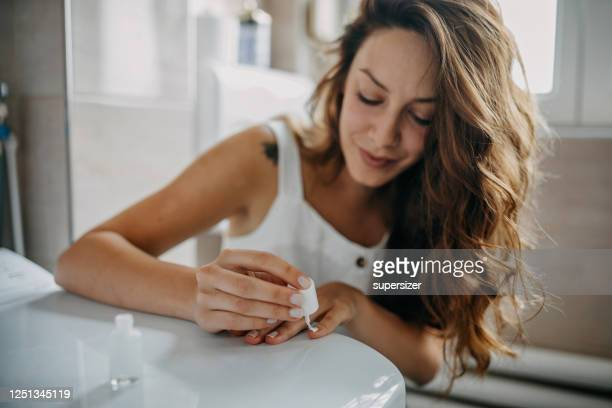 young woman paints her nails - good condition stock pictures, royalty-free photos & images