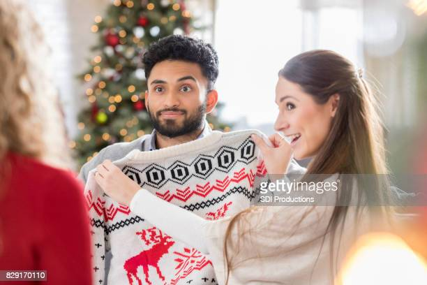 Young woman participates in ugly Christmas sweater gift exchange