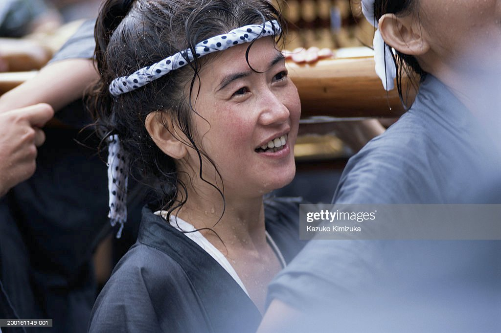 Young woman participating in water sprinkling festival : Stock-Foto