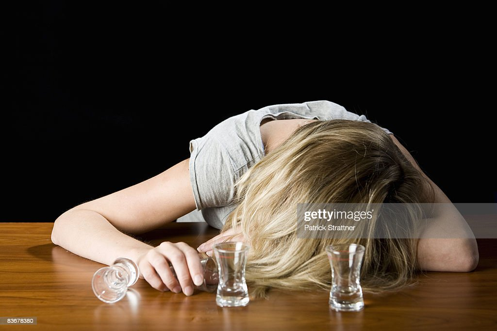 A young woman passed out drunk on a bar counter : Stock Photo