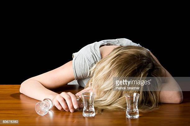 a young woman passed out drunk on a bar counter - drunk woman stock pictures, royalty-free photos & images