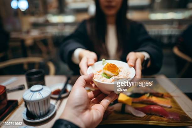 young woman passing a bowl of seafood donburi across table to a friend during lunch in a japanese restaurant - 人体部位 ストックフォトと画像