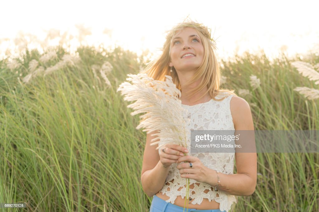 Young woman pauses in field of rushes, sunrise : Stock Photo