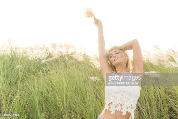 Young woman pauses in field of rushes, sunrise