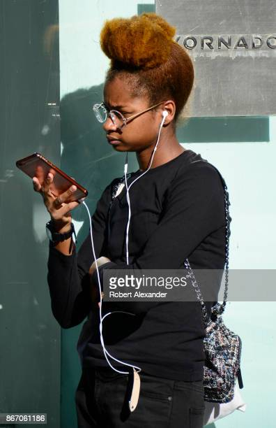 A young woman pauses on a New York City sidewalk to use her smartphone