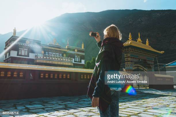 Young woman pauses outside of Tibetan Buddhist monastery