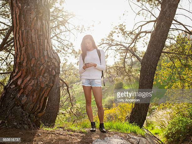 young woman pausing on hike to check phone - beautiful filipino women stock photos and pictures