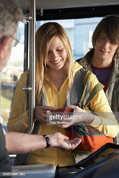 young woman paying bus fare to driver, smiling - fare stock pictures, royalty-free photos & images