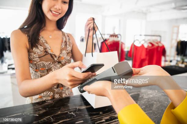 young woman paying contactlessly - merchandise stock pictures, royalty-free photos & images