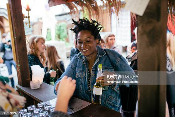 Young Woman Paying For Drink At Bar In Open Air Club