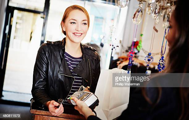 Young woman paying for shopping using credit card