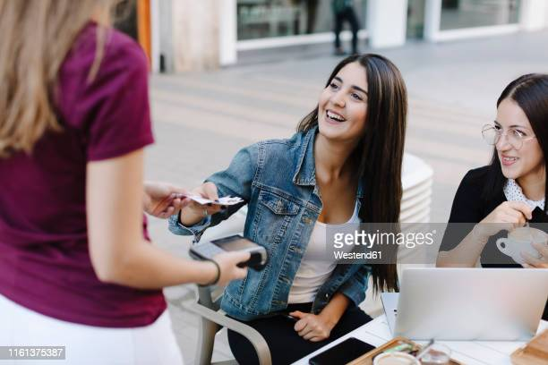 young woman paying in a cafe - coupon stock pictures, royalty-free photos & images