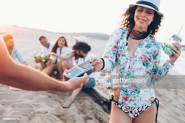 Young woman paying with credit card on beach