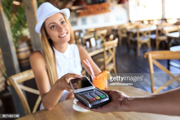 Young woman paying with smart phone in cafeteria