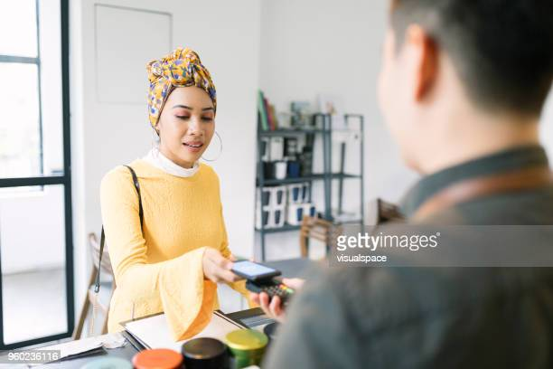 young woman paying with smartphone in a cafe - malaysia stock pictures, royalty-free photos & images