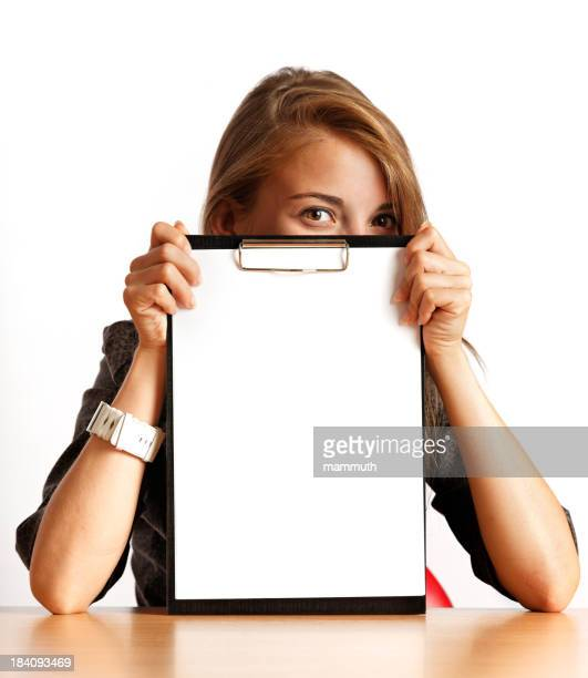 young woman peeking out behind a clipboard with blank paper