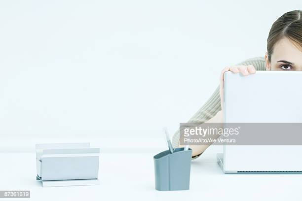 young woman peeking over laptop, cropped view - shy stock photos and pictures