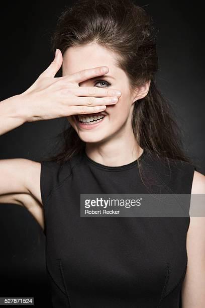 young woman peeking - augen zuhalten stock-fotos und bilder