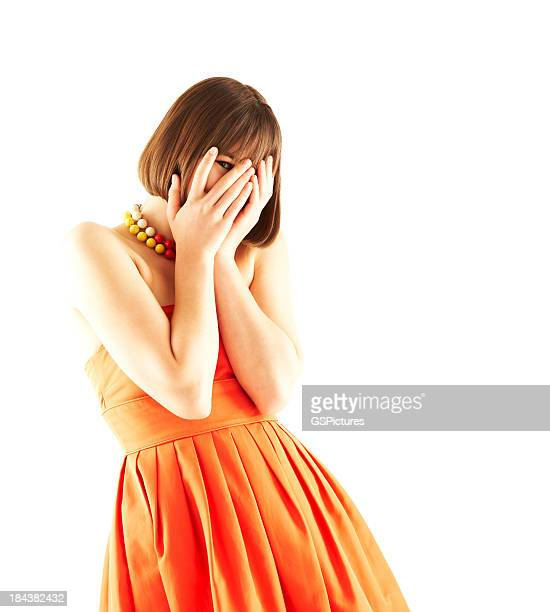 young woman peeking through covered face - orange dress stock pictures, royalty-free photos & images