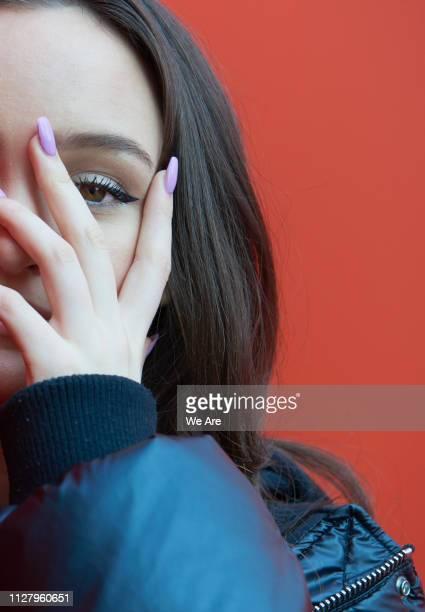 young woman peeking through fingers. - farbquadrat stock-fotos und bilder