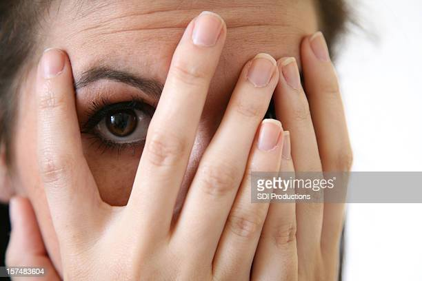Junge Frau Spähen durch die Finger