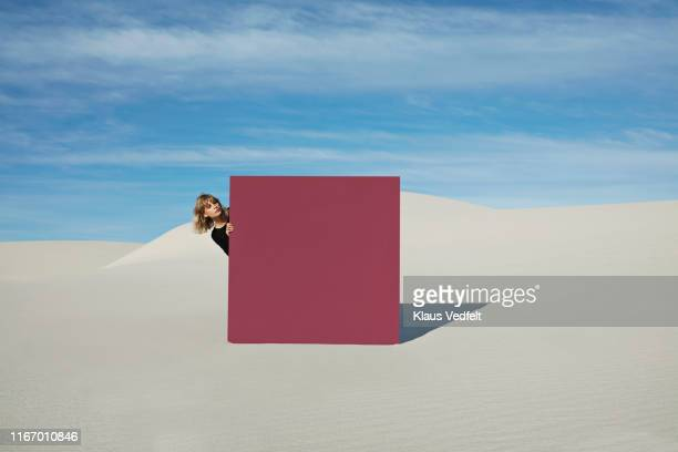 young woman peeking through maroon portal at desert against sky - curiosity stock pictures, royalty-free photos & images