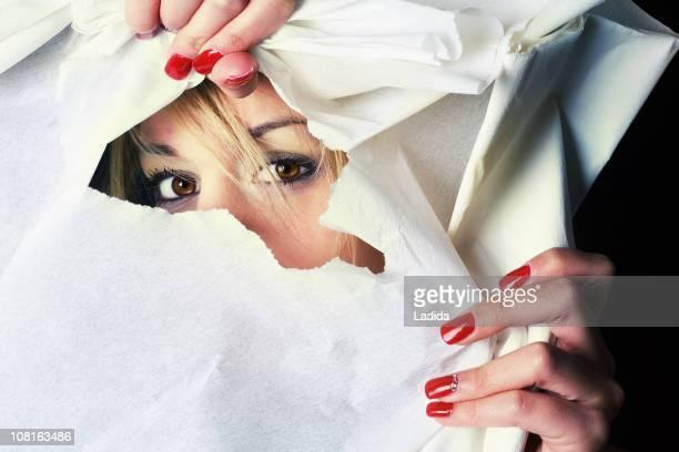 若い女性を通してのぞく破れたホールの紙 - peeping holes ストックフォトと画像