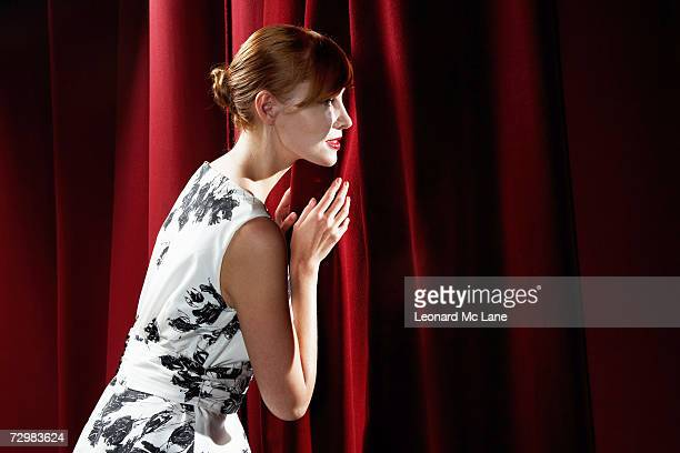 young woman peeking through stage curtain - あがり症 ストックフォトと画像