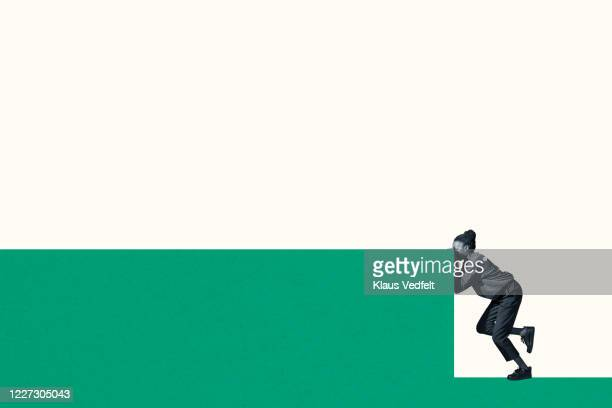 young woman peeking while standing on green wall - pushing stock pictures, royalty-free photos & images