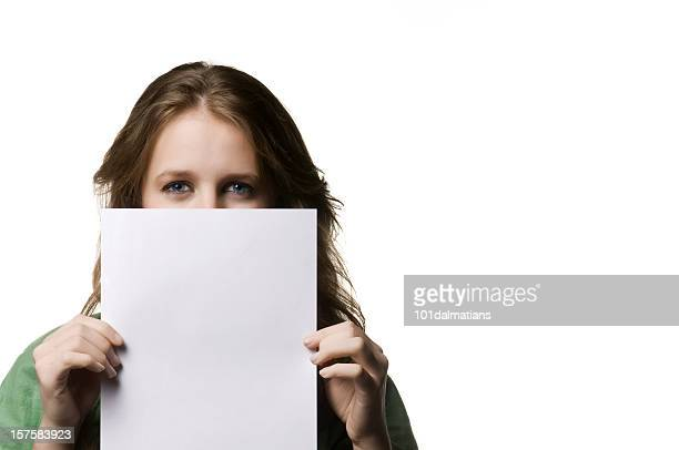 A young woman peeks over a blank white paper