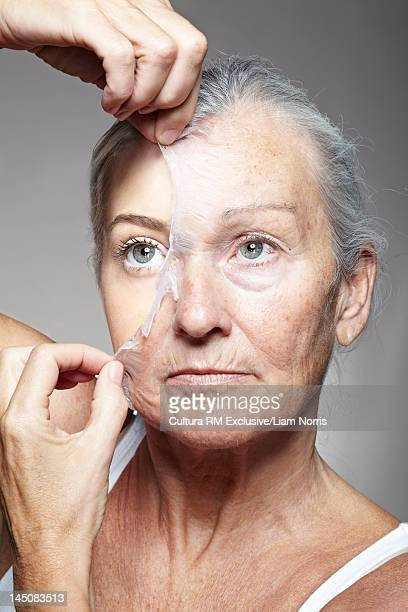 Young woman peeling off old mask