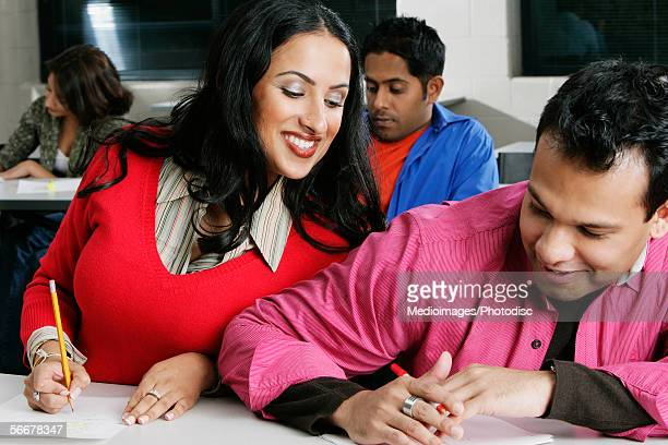 Young woman peeping at a young man's paper in a classroom