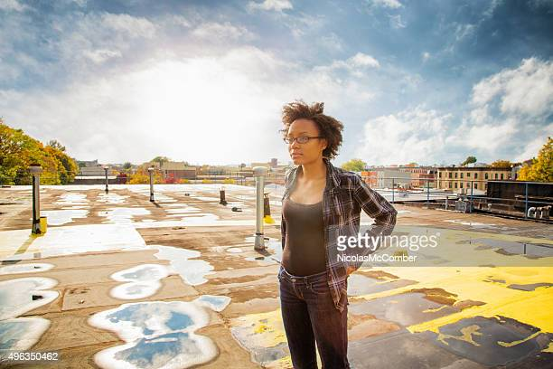 Young woman pensive on wet urban rooftop