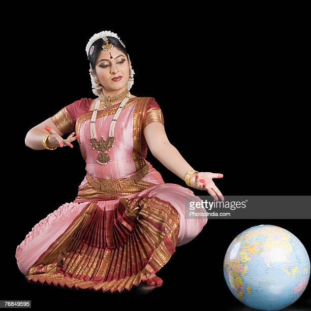 Young woman performing Bharatnatyam and gesturing towards a globe