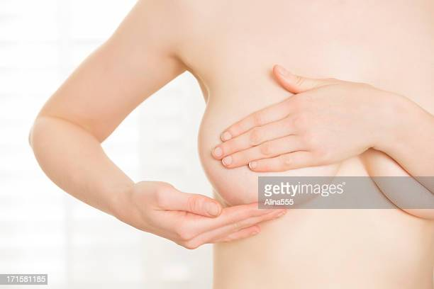 Young woman performing breast cancer self-exam