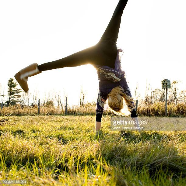 Young woman performing cartwheel in field
