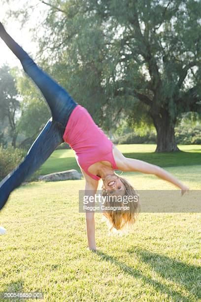 Young woman performing cartwheel on grass, smiling, (blurred motion)
