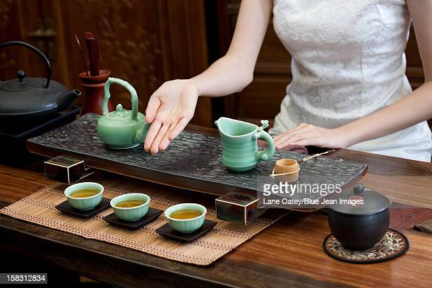 young woman performing chinese tea ceremony - ceremony stock pictures, royalty-free photos & images