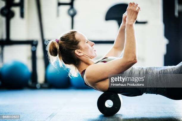young woman performing floor exercises at gym - routine stock-fotos und bilder