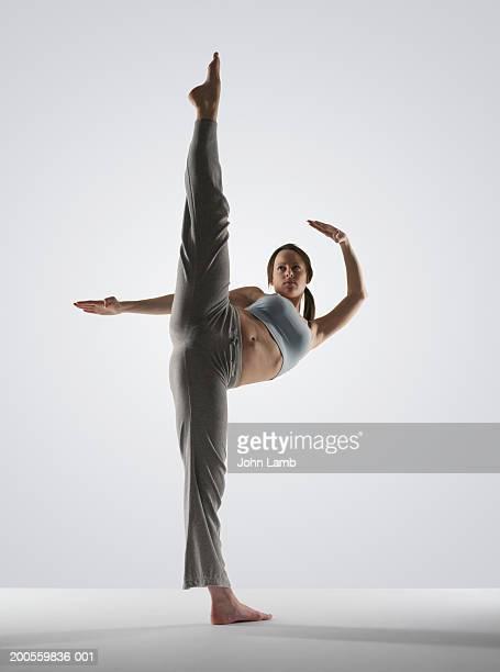 Young woman performing high kick