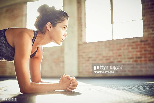 Young woman performing plank position in gym