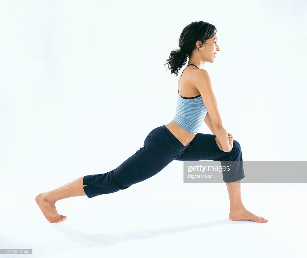 Young woman performing stretching exercise, side view : Stock Photo