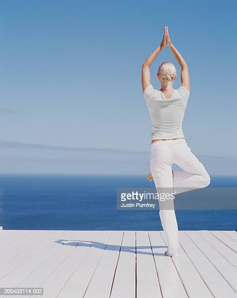 Young woman performing tree pose on decking, rear view