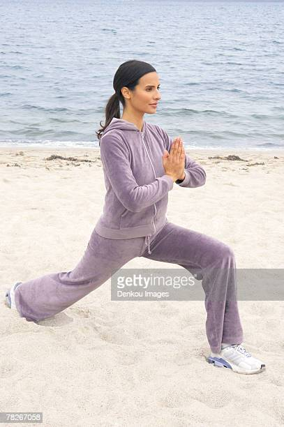 Young woman performing yoga on the beach