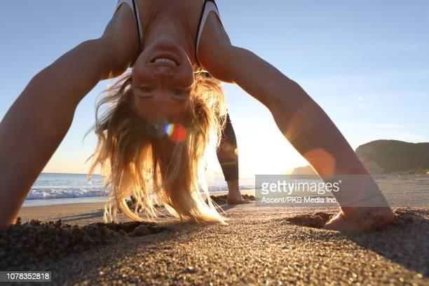 young woman performs handspring on beach - 20 24 jahre stock-fotos und bilder