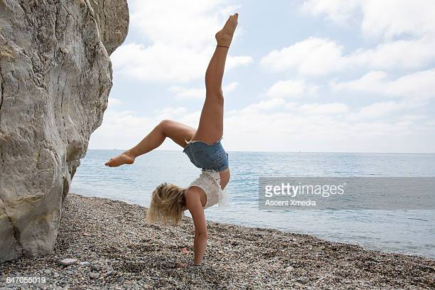Young woman performs handstand on pebble beach