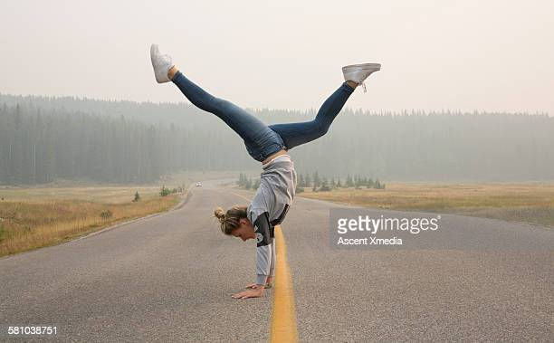Young woman performs handstand on rural road